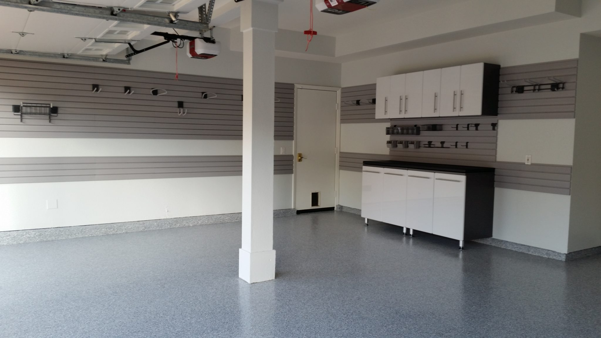 garage with cabinets and slat wall accessories